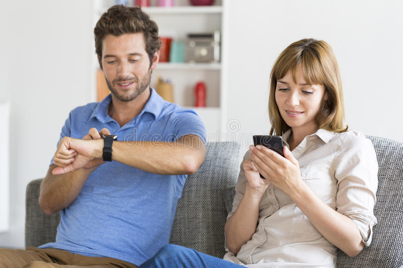 Digital geek couple. Mobile phone, smart watch. Modern white apartment. Super connected men and women at home with smart phone and connected watch royalty free stock photos