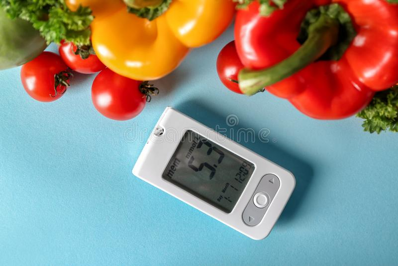 Digital glucometer med sund mat på färgbakgrund Sockersjuka bantar arkivbild