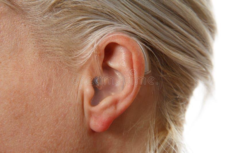 Digital hörapparat i öra för kvinna` s arkivfoto