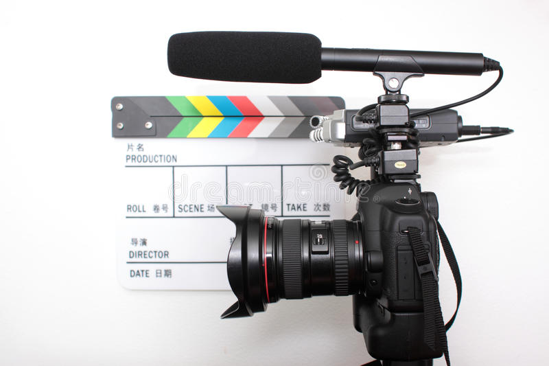 Digital high definition SLR camera. With audio equipment next to a clapperboard royalty free stock image
