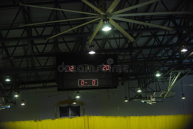 Digital indoor main scoreboard score. Volleyball players are on a field. stock photography
