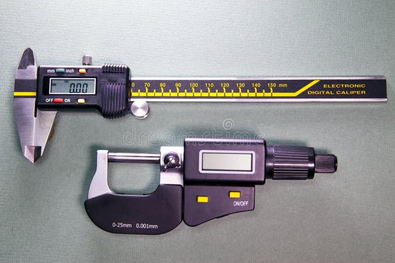 Digital klämma och en digital mikrometer arkivfoto