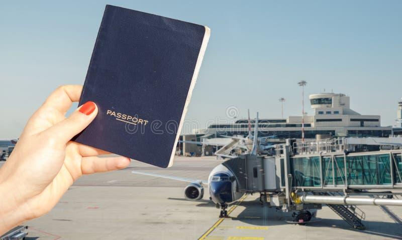 Digital komposit av handen som rymmer ett generiskt pass med den upptagna flygplatsterminalen arkivfoton