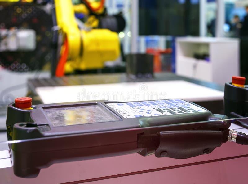 Digital kontrollant For Robot i fabrik mot bakgrunden av suddiga gula industriella robotar royaltyfri fotografi