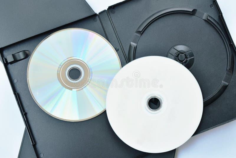 Digital m?ngsidig diskett eller DVD med den svarta plast- asken som f?rpackar p? vit bakgrund arkivfoton