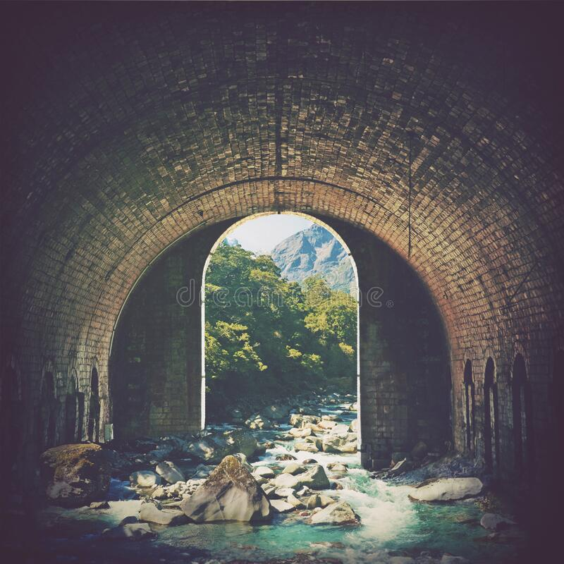 Digital manipulation of an historic arched brick tunnel as gateway to wilderness. Digital photo manipulation of an alpine mountain stream running through an old royalty free stock photos