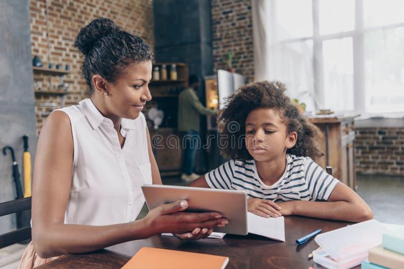 Digital minnestavla för modervisningflicka royaltyfria bilder