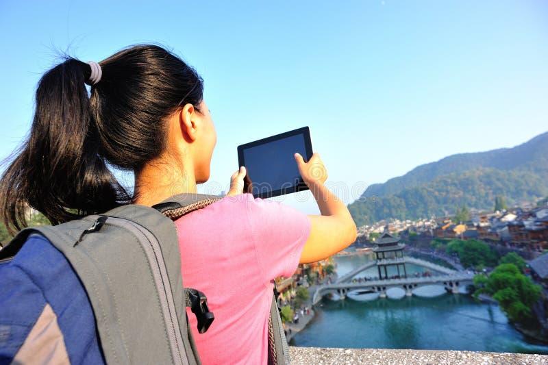 Digital minnestavla för ungt asiatiskt kvinnabruk arkivbilder