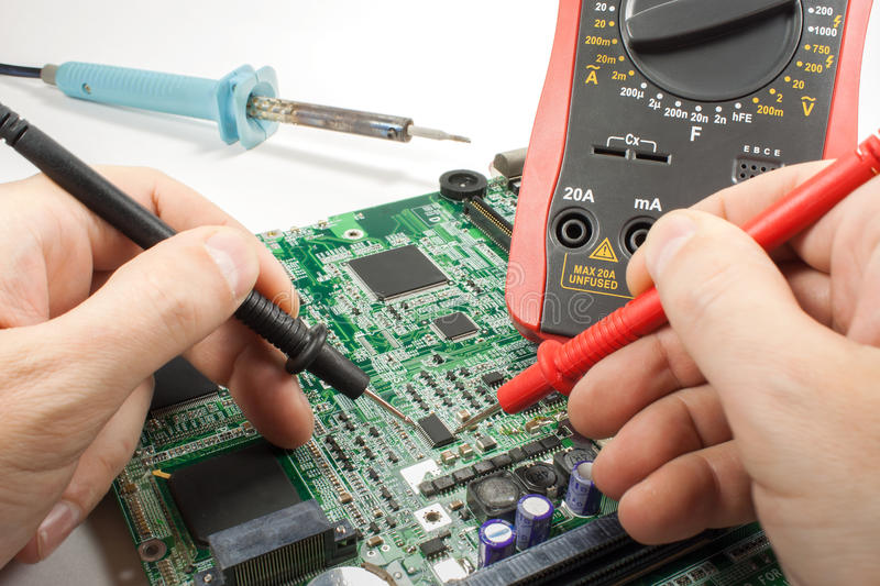 Digital multimeter with probe and soldering iron in the engineer`s hands in a workshop stock photo