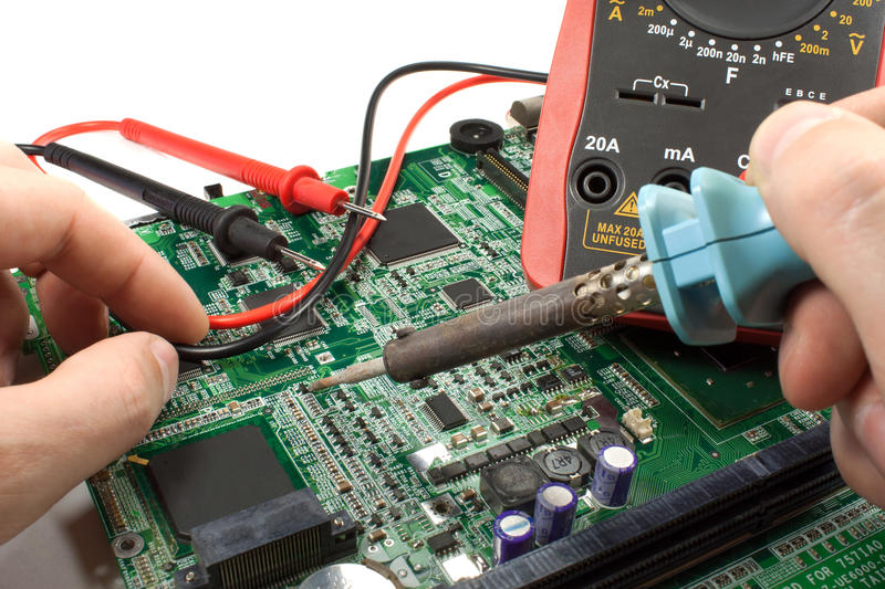 Digital multimeter with probe and soldering iron in the engineer`s hands in a workshop royalty free stock photo