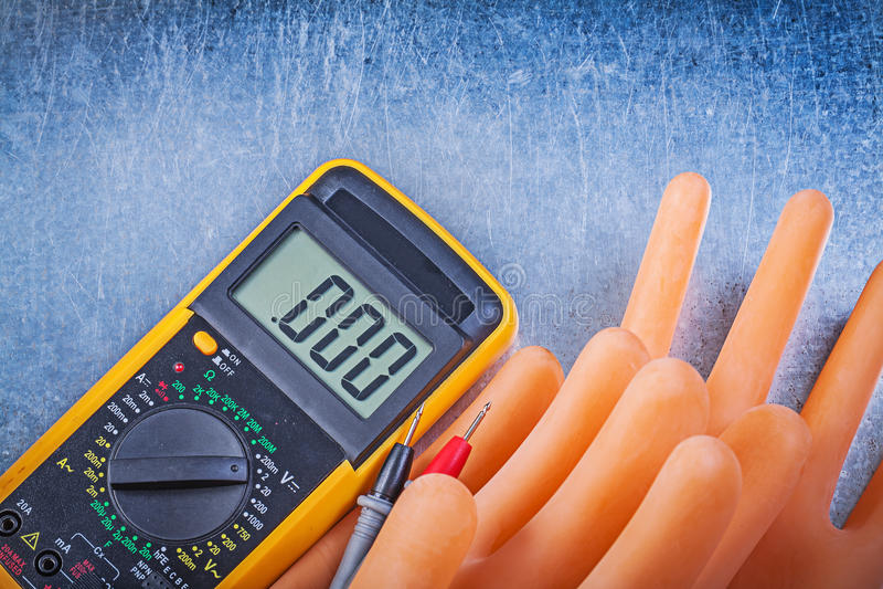Digital multimeter som isolerar rubber handskar på metallisk backgrou royaltyfri fotografi