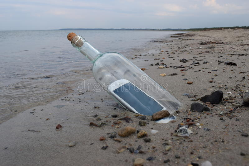 Digital native castaway sending a help message in a bottle.  royalty free stock images