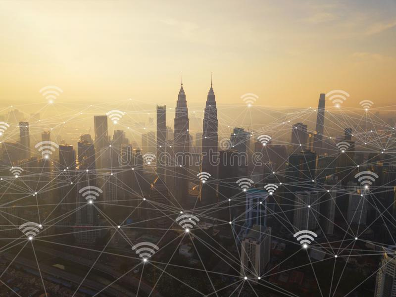 Digital network connection lines and wifi icons with Kuala Lumpur Downtown, Malaysia. Financial district in smart city in stock image