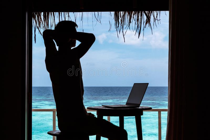 Silhouette of a young man relaxing while working with a computer on a table. Clear blue tropical water as background royalty free stock images