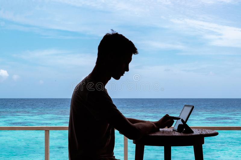 Silhouette of a young man working with a tablet on a table. Clear blue tropical water as background. Digital nomad concept. working in the maldives royalty free stock photography