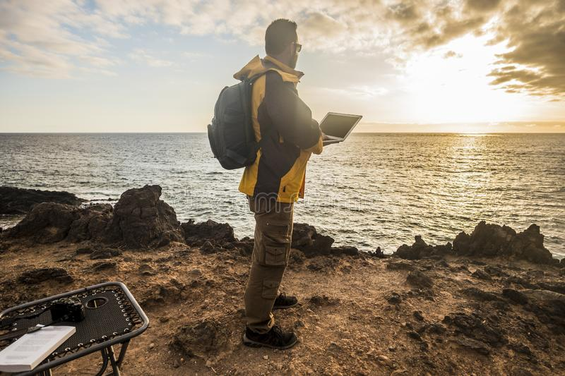 Digital nomad traveler man at work lokking an amazing golden sunset on the ocean. camera and laptop and beautiful lifestyle in royalty free stock photography