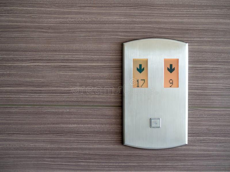 Digital nummer och ner pil på metallisk hissappellpanel på trämodellväggbakgrund royaltyfri bild