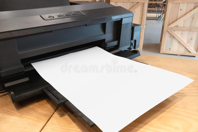 Digital paper printer and blank template on wooden table stock photo