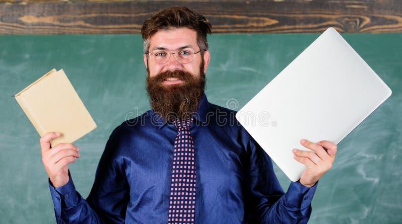Digital przeciw papierowi Nauczyciela modnisia brodaci chwyty książka i laptop Co ty wolał Nauczyciela wybierać nowożytny obrazy stock