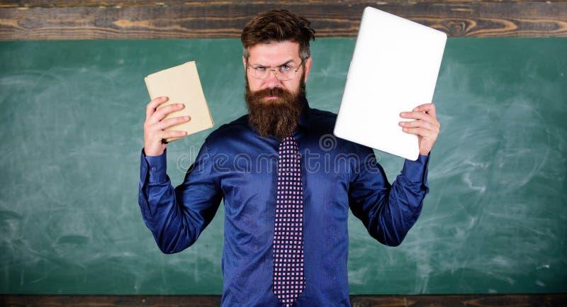Digital przeciw papierowi Nauczyciela modnisia brodaci chwyty książka i laptop Co ty wolał Nauczyciela wybierać nowożytny zdjęcie royalty free