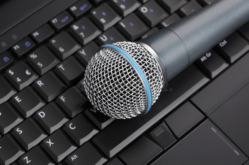 Digital recording. Professional microphone on laptop keyboard stock image
