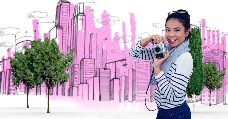 Digital sammansatt bild av den hållande kameran för kvinna mot byggnader arkivfoto