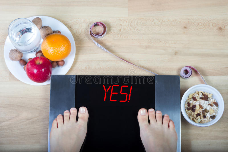 Digital scales with female feet on them and sign `yes!` surrounded by healthy food. Digital scales with female feet on them and sign`yes!` surrounded by glass stock photos