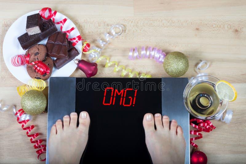 Digital-Skalen mit Frauenfüßen auf ihnen und Zeichenzeichen ` OMG! ` umgeben durch Weihnachtsdekorationen und ungesundes Lebensmi lizenzfreie stockbilder