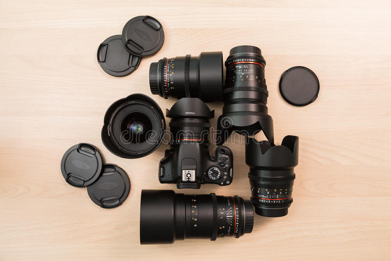 Digital SLR camera and a few interchangeable manual lenses. The equipment for filmmaking. The wooden table royalty free stock image