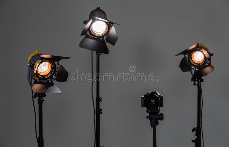 Digital SLR camera and three spotlights with Fresnel lenses. Manual interchangeable lens for filming royalty free stock photos