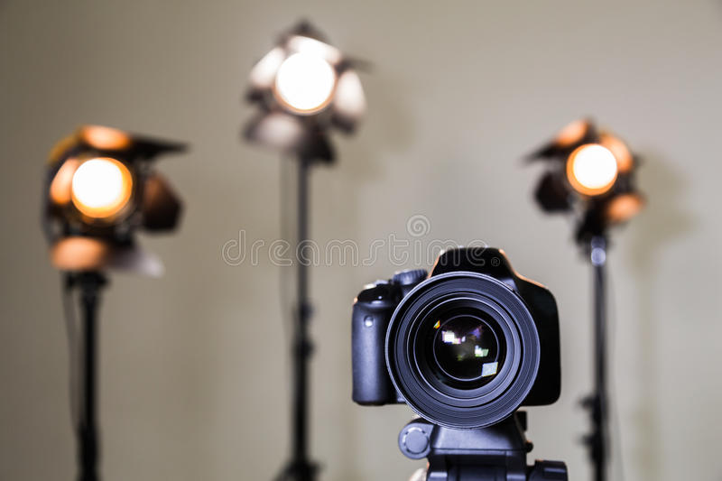 Digital SLR camera and three spotlights with Fresnel lenses. Manual interchangeable lens for filming stock images