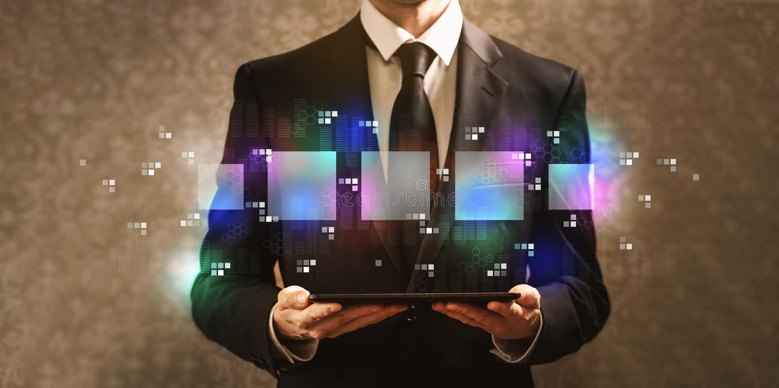 Digital square boxes with businessman holding a tablet computer royalty free stock photography