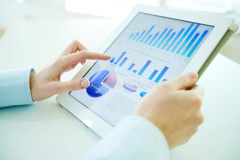 Digital statistics. Business person analyzing financial statistics displayed on the tablet screen