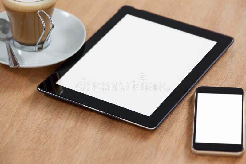 Digital-Tabelle und -Handy mit Tasse Kaffee stockfotografie
