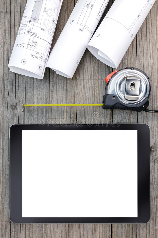 Digital tablet with architectural blueprints rolls and tape meas. Architectural blueprints with tape measure and tablet on gray wooden boards stock photography