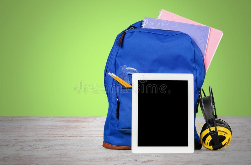 Digital tablet and backpack on the table stock image