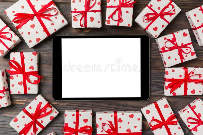 Digital tablet blank screen with gift box and hearts decor on wooden table. Top view. Valentines Day or other holidays concept royalty free stock images