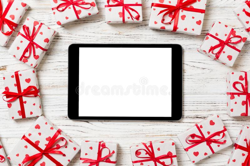 Digital tablet blank screen with gift box and hearts decor on wooden table. Top view. Valentines Day or other holidays concept royalty free stock photography