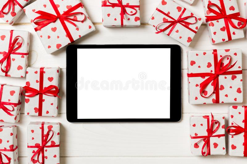 Digital tablet blank screen with gift box and hearts decor on wooden table. Top view. Valentines Day or other holidays concept royalty free stock image