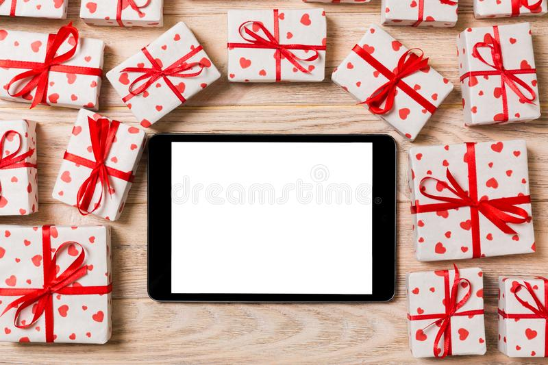Digital tablet blank screen with gift box and hearts decor on wooden table. Top view. Valentines Day or other holidays concept stock photo