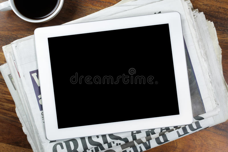 Digital tablet with blank screen on newspaper stock photography