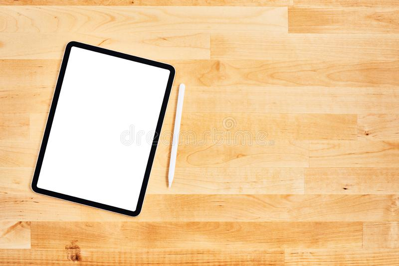 Digital tablet with blank white screen and pen on wooden office desk stock photography