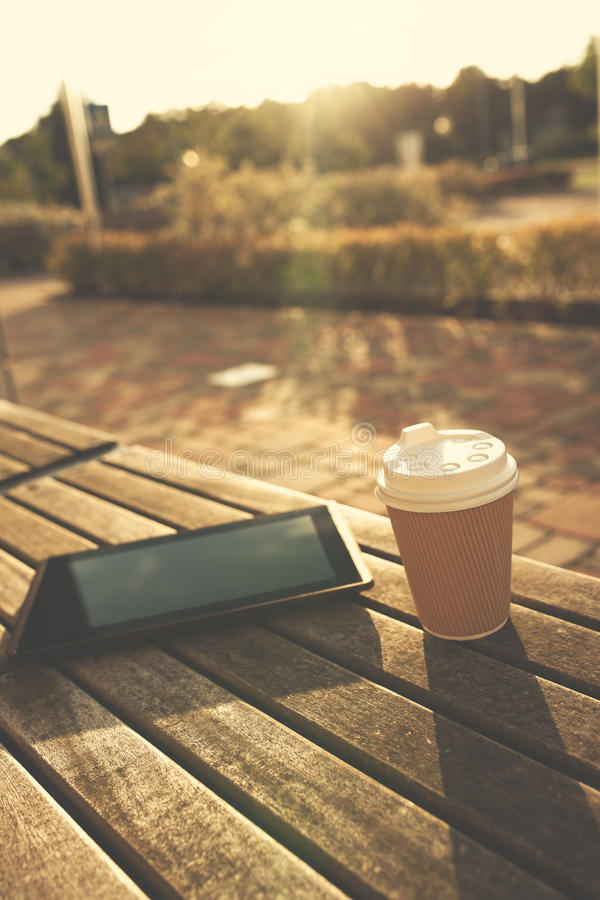 Digital tablet and cup of coffee on bench. Digital tablet and paper cup on wooden bench in sunshine royalty free stock photo