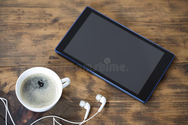 Digital tablet and a cup of coffee stock images