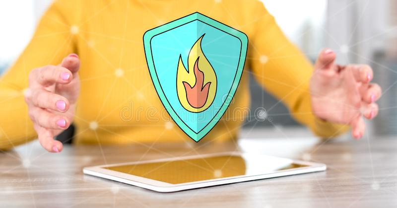 Concept of fire protection. Digital tablet with fire protection concept between hands of a woman in background stock photography