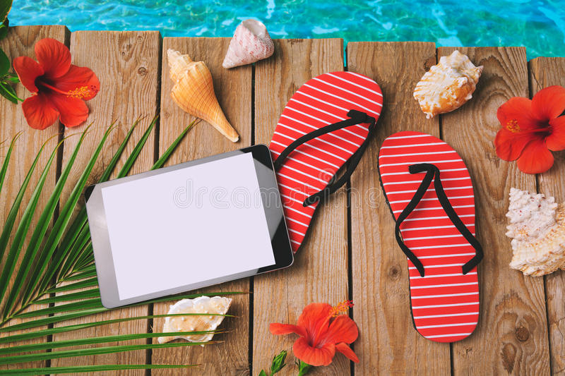Digital tablet, flip flops and hibiscus flowers on wooden background. Summer holiday vacation concept. View from above. Digital tablet, flip flops and hibiscus stock photos