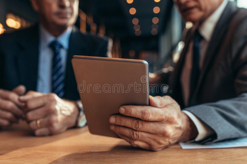 Digital tablet in hand of businessman talking to his partner stock photos
