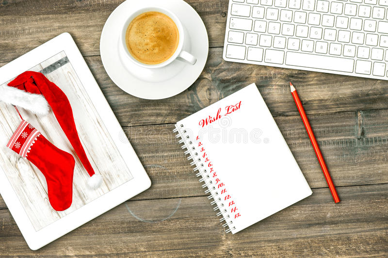 Digital tablet, keyboard coffee drink. Christmas Wish list royalty free stock images