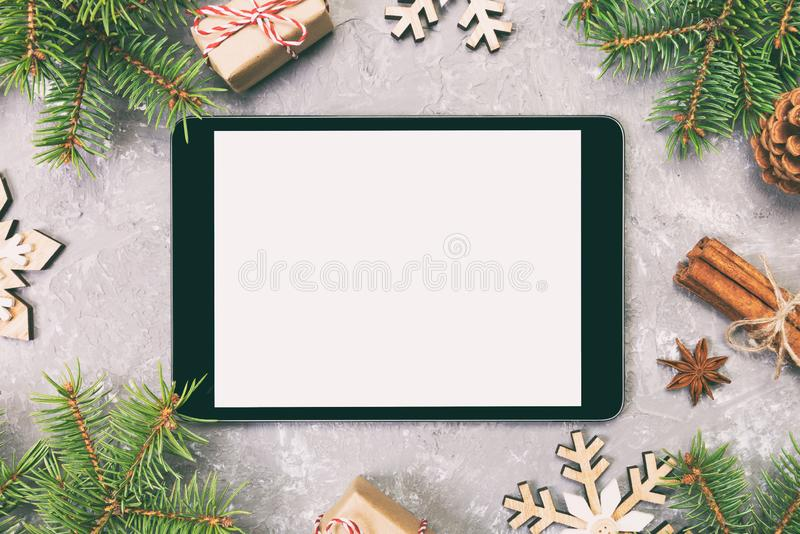 Digital tablet mock up with rustic Christmas gray cement background decorations for app presentation. top view with copy space. royalty free stock images