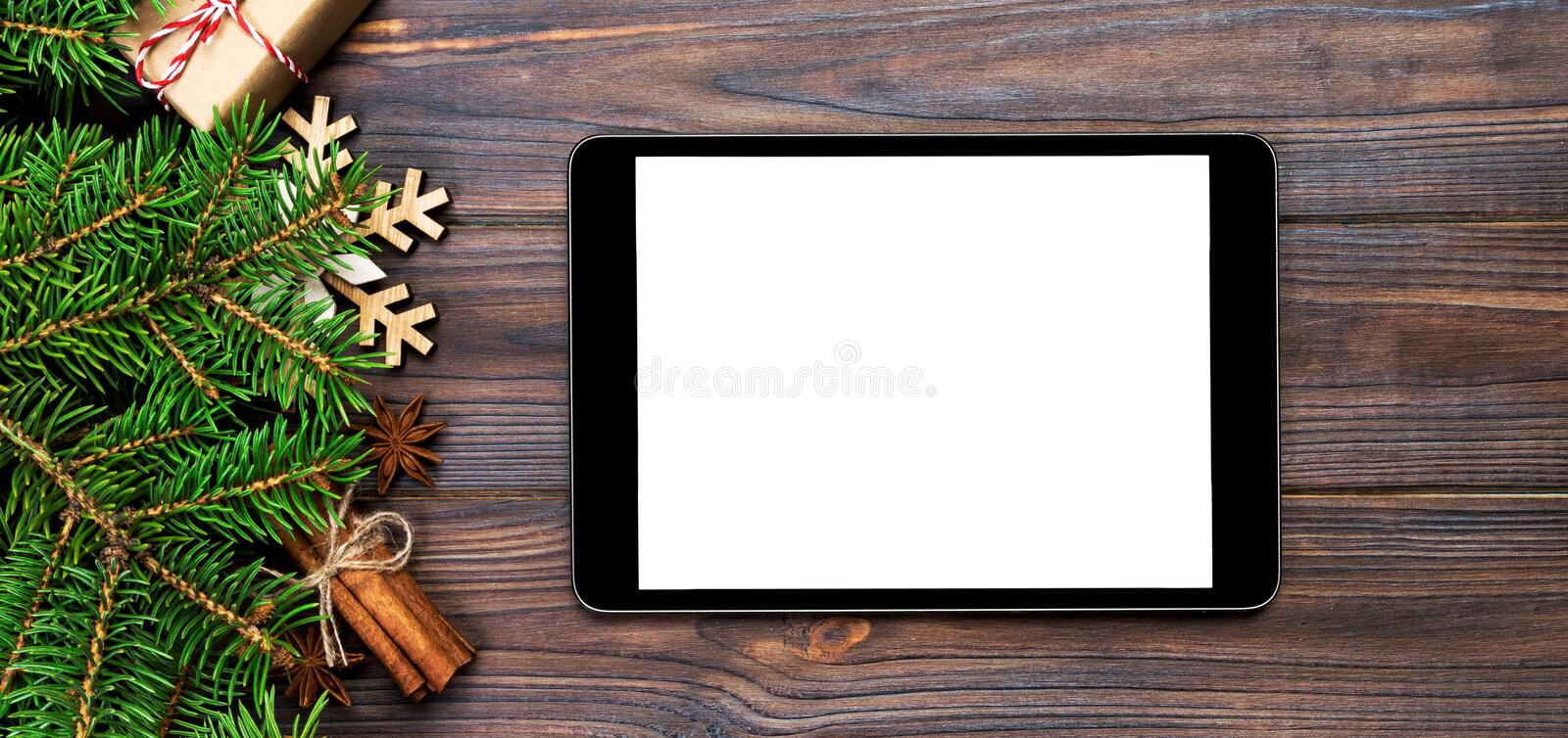 Digital tablet mock up with rustic Christmas wood background decorations for app presentation. top view banner with copy space royalty free stock photos